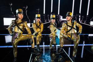 Neljä kultaisiin, kireisiin catsuiteihin pukeutunutta tanssijaa poseeraa UMK-lavalla. Päässä kultainen ns. tinasotilashattu.