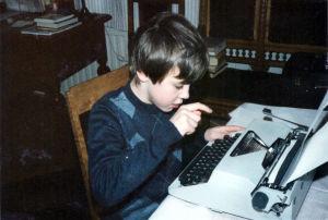 Kymmenvuotias Kalle Kallio kirjoittaa kirjoituskoneella näytelmää istuen puisella tuolilla ikkunan lähellä.