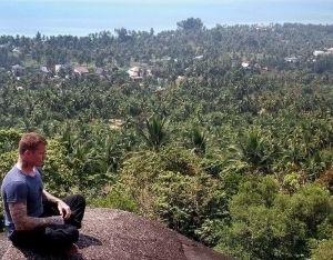 Ex-thainyrkkeilijä Jarkko Stenius meditoi kivellä, kaunis vehreä thaimaalainen maisema, kuvattu vuonna 2011.