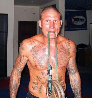 Ex-thainyrkkeilijä Jarkko Stenius treenaa Phuketissa 2008. Tatuoitu mies nostaa painoa hampaillaan.