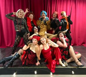 Burleskiryhmä Aistikkaat poseeraa yhdessä teatterin lavalla