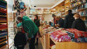 Affär med samiska hantverk, böcker, kort och tyger. Kunder tittar på olika föremål som är till salu, en försäljare hjälper till.