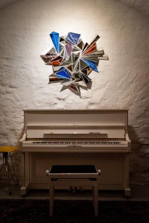 Piano i källarvalv med spegelkonstverk på väggen ovanför.