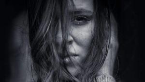 Naisen kasvot, hiuksia kasvojen edessä, kyynel poskella, mustavalkoinen.