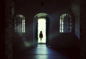 Pieni lapsi seisoo kartanon oviaukossa