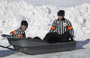 Kaksi jääkiekkotuomaria istuu isossa pulkassa ulkojäällä.