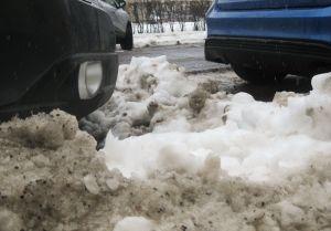 Kaksi autoa parkkeerattuna tien varteen lumikinosten sekaan