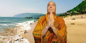 Mies seisoo kämmenet vastakkain rannalla Intiassa?