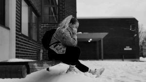 Tyttö istuu talvella yksin rakennuksen rappusella reppu selässään.än