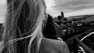 Nuori vaaleahiuksinen nainen tukka hulmuten Linnanmäen vuoristoradassa kuvattuna takaapäin