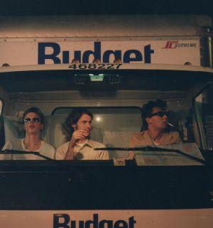 """Kolme nuorta miestä istuu vierekkäin muuttoauton etupenkillä. Kuva on otettu etulasin lävitse. Kuljettaja polttaa tupakkaa tummissa aurinkolaseissa. Konepellissä lukee """"Budget""""."""