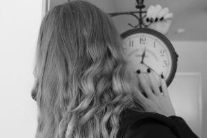 Nainen pitelee isoa kelloa käsissään