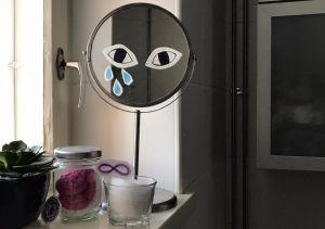 Meikkipeili johon on liimattu kankaasta silmät ja kyyneleitä
