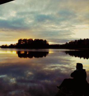 Mies istuu iltahämärässä järven rannalla, vedestä heijastuvat pilvet ja auringonlaskun kajo ja saari kauempana.