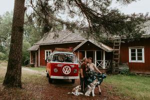 Ett par och två hundar samt en röd bil framför ett gammalt hus med röd brädfodring och vita knutar.