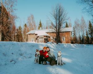 En familj framför ett stort trähus i vinterlandskap.