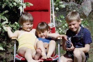 Marikki kainalossaan Riikka istuu kesäisellä pihalla aurinkotuolilla, veli Jyrki on kumartunut kameran kanssa heidän viereensä.