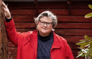 MArikki HAkola seisoo hirsirakennuksen punamultaisen seinän edessä punainen takki päällään.