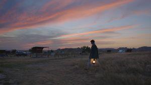 Nainen kävelee preerialla lyhdyn kanssa.