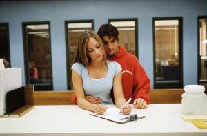 Teini-ikäinen tyttö ja poika seisovat pöydän ääressä vierekkäin tytön täyttäessä kaavaketta. Tytöllä on sininen paita, pojalla punainen huppari.
