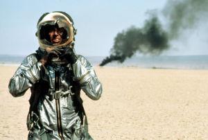 Hävittäjälentäjän pukuun pukeutunut mies kävelee aavikolla poispäin onnettomuuspaikasta, josta nousee savua. Miehen visiiri on hajonnut kokonaan.