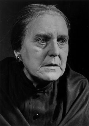 Svartvitt foto av en sträng gammal kvinna i svart.