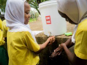 Kenialaisen Makongenin kylän lapset pesevät käsiään. Vesiastiassa lukee hyväntekeväisyysjärjestö Home Street Home -nimi.