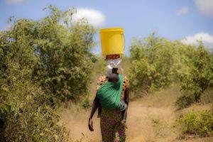 Nainen kantaa vesiastiaa päänsä päällä ja lasta selässään Kenian Nassarianin kylässä.