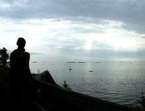 Nainen meren rannalla katsoo poispäin kamerasta, kohti horisonttia.