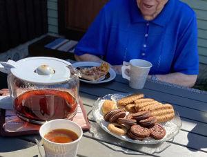 Vanhus istuu kahvipöydän ääressä. Hänestä näkyy kasvot suuhun asti, eli henkilö on tunnistamaton.