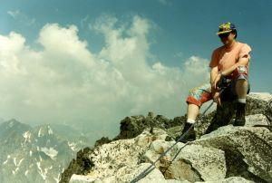 Vuorikiipeilyä harrastava mies istuu kalliolla. Hän on kiinni turvavaljaassa. Päässä on lippalakki.