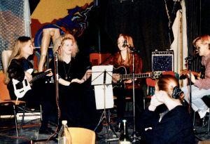 Opiskelijoiden bändi soittamassa tuoleilla istuen. Kuvassa viisi soittajaa sekä vahvistimia, nuottitelineitä ja mikrofonitelineitä.