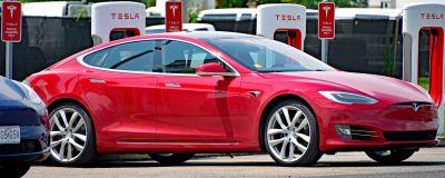 En röd bil med står parkerad framför laddstationer för elbilar.