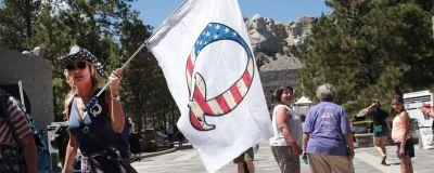 Qanon-protest i USA. En kvinna viftar med en flagga som har ett Q på sig. Bokstaven är färgad i USA:s flaggas färger.