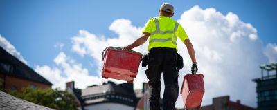 En man som jobbar vid en byggarbetsplats bär på två ämbare.