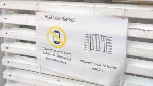 """En lapp där det stårpå finska """"Föräldrar! Vi önskar att du inte använder telefonen då du lämnar eller hämtar ditt barn."""""""