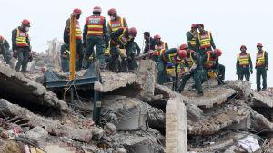 Paktistanska räddningsarbetare försöker hitta offer efter fabriksras utanför Lahore.