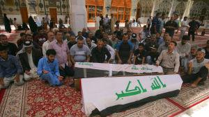 Släktingar begraver offer i terrordåd i Bagdad i offrens hemstad Najaf.