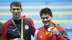Två simmare med varsin medalj av olika valör.
