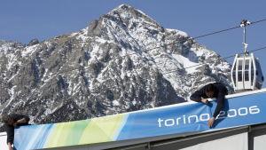 Miehet ripustavat Torinon v. 2006 talviolympialaisten banderollia, taustalla Alppien huippu ja hiihtohissi.
