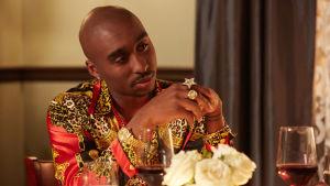Tupac Shakur (Demetrius Shipp Jr) sitter vid ett middagsbord iklädd en grann skjorta och guldsmycken.