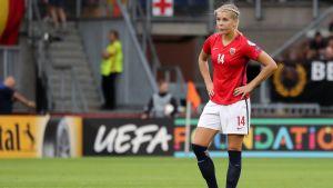 Ada Hegerberg står på en fotbollsplan.
