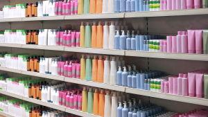 Omärkta tvål- och schampoflaskor i olika färger står radade på hyllor.