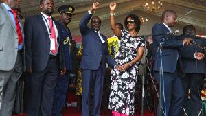 Robert Mugabe (mitten t.v) och hans fru Grace (mitten t.h.) anländer till lördagens födelsedagsfirande.