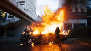 Två unga män står vid en brinnande bil i förortsmiljö.