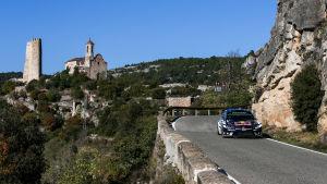 Sebastien Ogier rattar sin rallybil på de slingriga bergsvägarna i Katalonien. I bakgrunden en kyrka på ett berg.