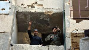 Syriska regeringssoldater visar segertecken i ett erövrat hus i Masaken Hanano