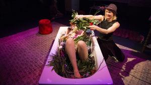 Johanna Dikert täcks av blommor i ett badkar av Johanna Holmström.