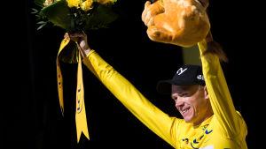 Chris Froome i den gula ledartröjan höjer upp blomkrans och mjukisdjur.