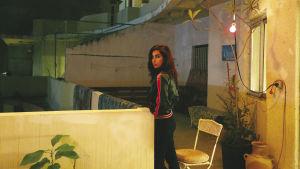 Yasmine Hamdan på en balkong på kvällen. en växt i kruka.